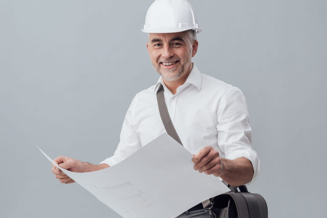 Professional architect checking a house blueprint, he is wearing a safety helmet