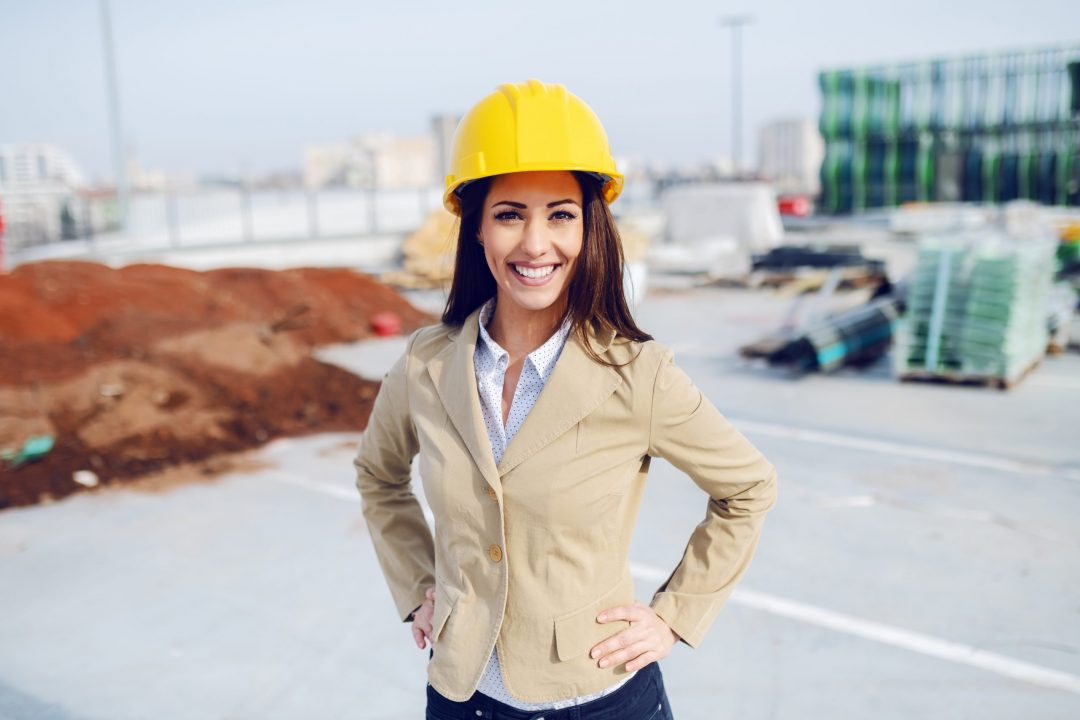 Portrait of gorgeous caucasian female architect in beige jacket and with protective helmet on head standing at construction site with hands on hips.